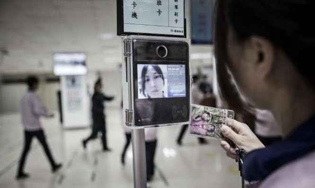 """Một nhân viên đang sử dụng thiết bị nhận diện khuôn mặt khi """"check in"""" để vào khu vực dây chuyền lắp ráp"""