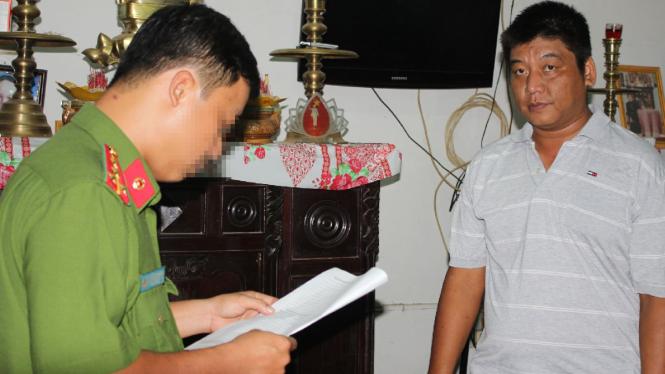 Công an đọc lệnh bắt tạm giam ông Bùi Văn Minh - Ảnh: Phan Tại/Tuổi trẻ