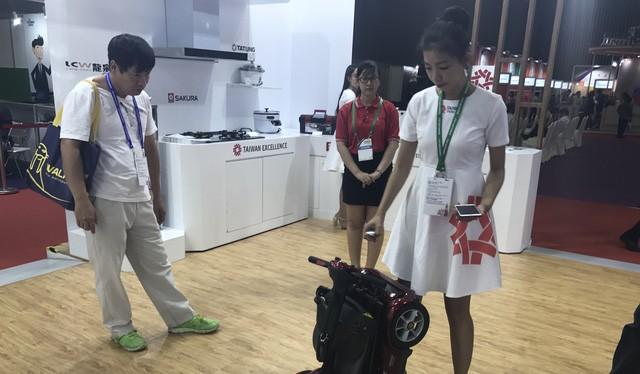 Khách tham quan xem giới thiệu về xe máy thông minh dành cho người tàn tật hay người già tại Taiwan Expo 2017 (TP.HCM) - Ảnh: T.Trực