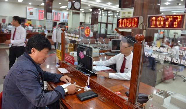 Khách hàng giao dịch tại một ngân hàng ở Q.1, TP.HCM - Ảnh: D.Ph.