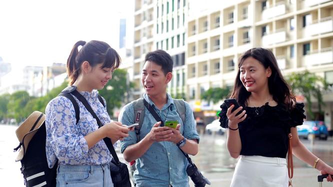 Các bạn trẻ sử dụng wifi miễn phí trên phố đi bộ Nguyễn Huệ. Nguồn Thanh Niên