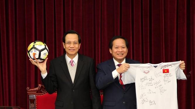 Bộ trưởng Bộ LĐ-TB&XH Đào Ngọc Dung (trái) và Bộ trưởng Bộ Thông tin và Truyền thông Trương Minh Tuấn nhận quả bóng và chiếc áo đấu của U23 Việt Nam tặng Thủ tướng Chính phủ để chuẩn bị đấu giá. Ảnh VGP