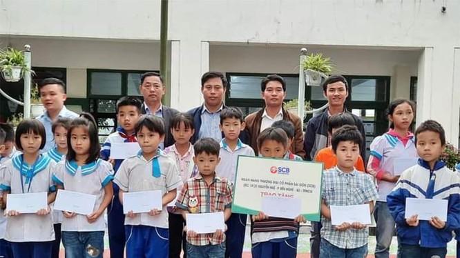Đại diện SCB trao quà và phần tiền ủng hộ cho các em học sinh mầm non và tiểu học Hồng Lộc, Thụ Lộc, huyện Lộc Hà, tỉnh Hà Tĩnh.