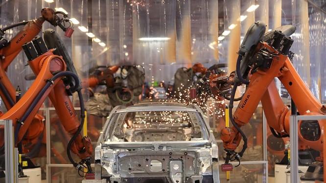 Cánh tay robot hoạt động trên dây chuyền sản xuất bên trong nhà máy VW ở Đức. (Ảnh: Bloomberg)