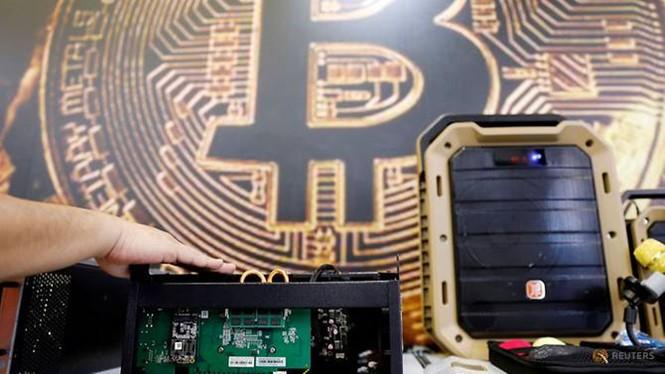 Thiết bị khai thác bitcoin trước logo đồng mã hóa, ảnh chụp ở Đài Loan hồi tháng 6. ẢNH: REUTERS