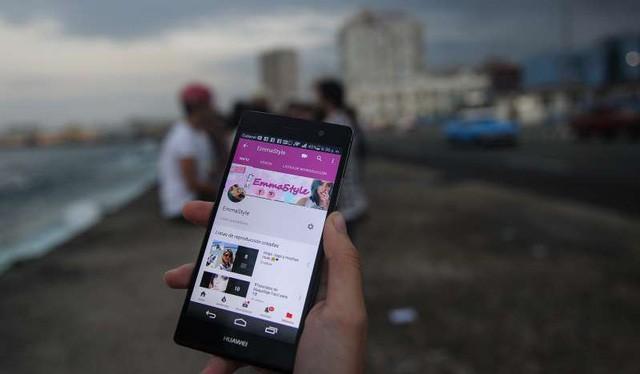 Một chủ tài khoản Youtube người Cuba đang giới thiệu kênh Youtube của cô trên điện thoại di động - Ảnh: AFP