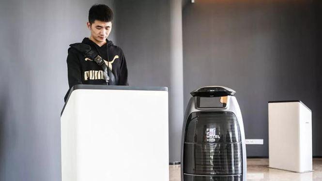 Khách tự làm thủ tục check-in với máy quét và robot đứng bên sẵn sàng trả lời câu hỏi. Ảnh: Radii China.