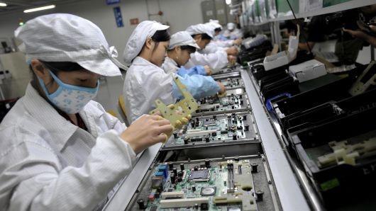 Công nhân đang lắp ráp các linh kiện điện tử tại nhà máy của Foxconn ở Trung Quốc. Ảnh: AFP.