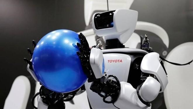 Robot T-HR3 của Toyota, nặng 75kg và cao 1,5m, đang cầm một quả bóng. Ảnh: Reuters.
