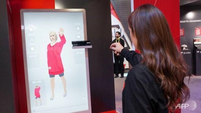 Nhân viên JD.com giới thiệu hệ thống AR cho phép khách hàng thử đồ ảo tại shop. Ảnh: AFP.