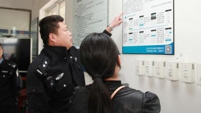 Một cảnh sát tại Bắc Kinh đang giải thích cho người nhà tù nhân về cách gửi tiền cho họ qua ứng dụng thanh toán Alipay.