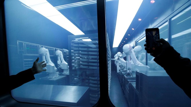 Một khách hàng chụp ảnh một cánh tay robot thu thập các món ăn đóng gói sẵn từ kho lạnh tại nhà hàng lẩu trí tuệ nhân tạo mới của Haidilao ở Bắc Kinh, Trung Quốc. Ảnh: Reuters