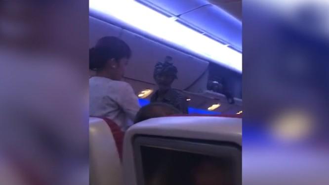 Một người đàn ông cầm túi nhựa đi xin tiền hành khách trên chuyến bay của hãng Qatar Airways (ảnh cắt từ clip)