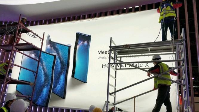 Các công nhân đang thi công poster quảng cáo điện thoại Huawei Mate X (ảnh: Phone Arena)