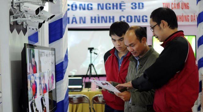 Khách tham quan nghe giới thiệu về thiết bị camera giám sát tại một triển lãm về thiết bị công nghệ