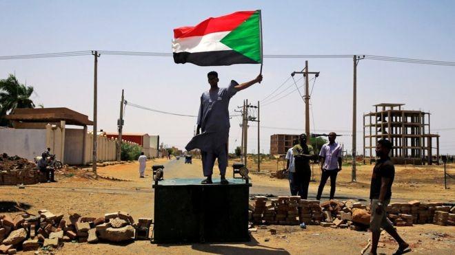 Một người biểu tình Sudan đứng trên hàng rào chắn ở Khartoum hôm thứ Tư (ảnh Reuters)