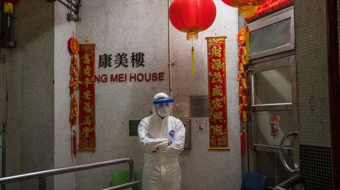 Một nhân viên y tế mặc đồ bảo hộ đứng bảo vệ bên ngoài lối vào tòa nhà chung cư ở Tsing Yi (Hồng Kông) sau khi phát hiện cư dân thứ hai nhiễm virus tại đây. Hơn 100 người sống tại tòa chung cư này đã được sơ tán (ảnh Getty Images)