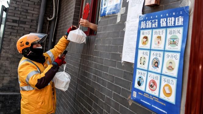 Một lái xe công nghệ nhận đồ ăn qua cửa sổ từ một nhà hàng ở Bắc Kinh