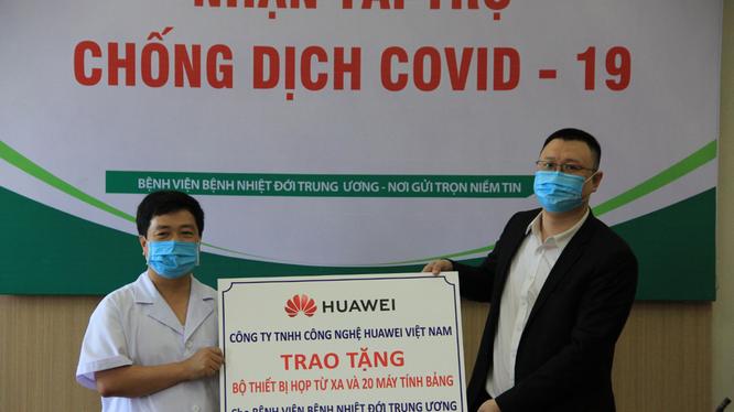 Ông Ma Yunhui, Phó tổng giám đốc Công ty TNHH Công nghệ Huawei Việt Nam (phải), đại diện công ty, trao tặng Bộ thiết bị giải pháp hội nghị truyền hình và 20 máy tính bảng cho ông Lê Văn Dụng, Phó Giám đốc Bệnh viện Bệnh Nhiệt đới Trung ương