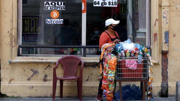 """Một người phụ nữ đi ngang qua một tấm biển có nội dung """"Bitcoin được chấp nhận ở đây"""". Bitcoin đã được chấp nhận làm phương tiện thanh toán ở El Salvador từ ngày 7/9"""