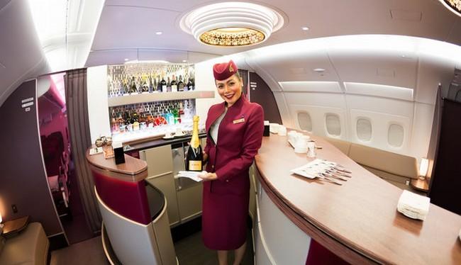 Một tiếp viên hàng không chào đón khách khi họ bước lên máy bay thuộc hãng Qatar Airways (Ảnh Shutterstock)