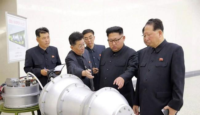 Nhà lãnh đạo Triều Tiên Kim Jong Un đứng trước một thiết bị được cho là đầu đạn hạt nhân thu nhỏ (Ảnh AP)