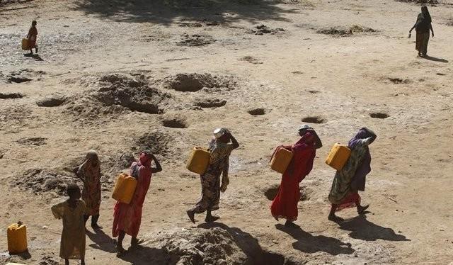 Những người phụ nữ đang mang các can nước được lấy từ giếng đào trên cát dọc theo bờ sông Shabelle, đây là khu vực rất thiếu nước trong mùa hạn tại Somali (Ảnh Reuters)