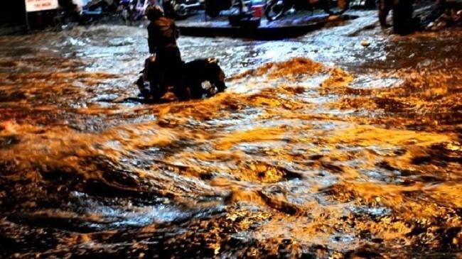"""Người dân TP. HCM """"bơi"""" trên đường khi triều cường - (Nguồn Internet)"""