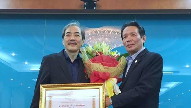 Thứ trưởng Bộ TT&TT Hoàng Vĩnh Bảo (bên phải) thừa ủy quyền Chủ tịch nước trao tặng Huân chương Lao động hạng Ba cho Phó Cục trưởng Cục Báo chí Vũ Thanh Sơn.