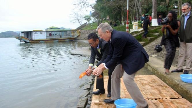 Đại sứ Mỹ Ted Osius và người bạn đời Clayton Bond cùng thực hiện nghi lễ thả cá chép trên sông Hương để tiễn đưa ông Công ông Táo về trời - Ảnh: Nguyên Linh