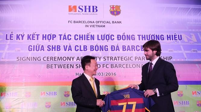 Ông Xavier Asensi - Giám đốc Điều hành khu vực Châu Á Thái Bình Dương CLB Barcelona (bên phải) tặng quà lưu niệm cho Ông Đỗ Quang Hiển - Chủ tịch HĐQT SHB, chiếc áo mang số 77 – là địa chỉ Trụ sở chính của SHB trên phố Trần Hưng Đạo