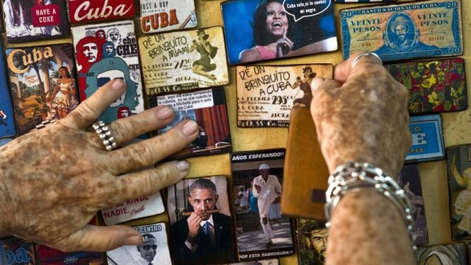 Một nghệ sĩ người Cuba trưng bày nhiều hình ảnh liên quan đến tổng thống Mỹ Barack Obama ở cửa hàng bán đồ lưu niệm tại thủ đô Havana, Cuba - Ảnh:AP