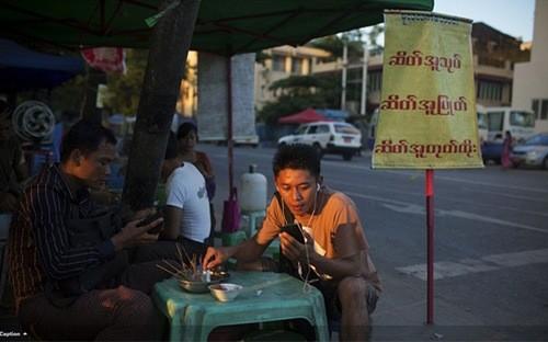 Sóng Viettel sắp chính thức phủ lên đất Myanmar. Trong ảnh là một người đàn ông Myanmar sử dụng điện thoại di động khi đang ngồi quán vỉa hè ở Yangon - Ảnh: Bloomberg.