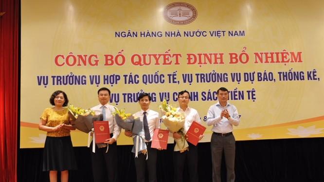 Thống đốc Lê Minh Hưng cùng Phó Thống đốc Nguyễn Thị Hồng trao Quyết định và tặng hoa chúc mừng các tân Vụ trưởng. (Ảnh: SBV)