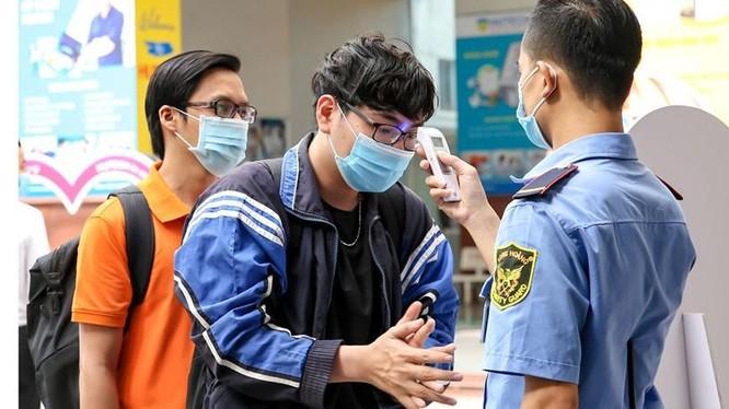 Sinh viên Đại học Công nghệ TPHCM được đo thân nhiệt, rửa tay bằng nước sát khuẩn trước khi vào trường. Ảnh: VNE