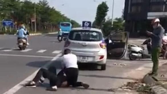 Hình ảnh từ video clip cho thấy Đại uý Công an gọi điện thoại trong khi người lái taxi vật lộn với tên cướp - Ảnh cắt từ clip