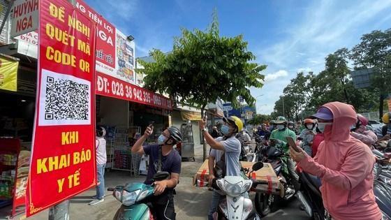 Người dân quét mã khai báo y tế trên điện thoại tại trạm kiểm soát trên đường Nguyễn Kiệm (Gò Vấp) ngày 7/6 (Ảnh: SGGP)