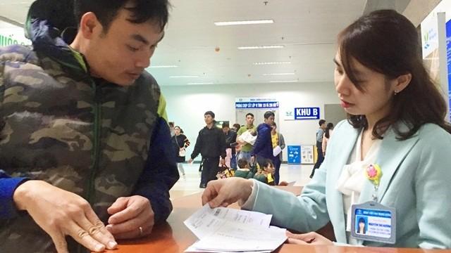 Một phụ huynh được nhân viên của Bệnh viện Nhi Trung ương hướng dẫn thủ tục thanh toán ra viện.