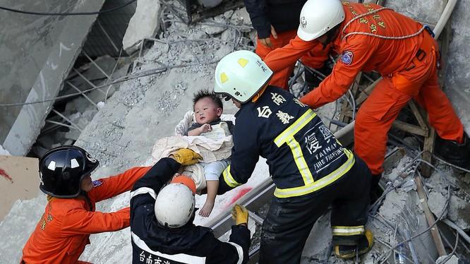Lực lượng cứu hộ giải thoát cho một đứa bé trong khu chung cư 17 tầng sau trận động đất ở Đại Nam (Đài Loan) hôm 6.2 - Ảnh: AFP