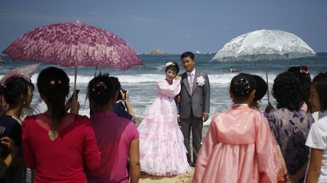 Cặp đôi mới cưới chụp ảnh trên bãi biển Sijung Ho trước sự chứng kiến của họ hàng và bạn bè.