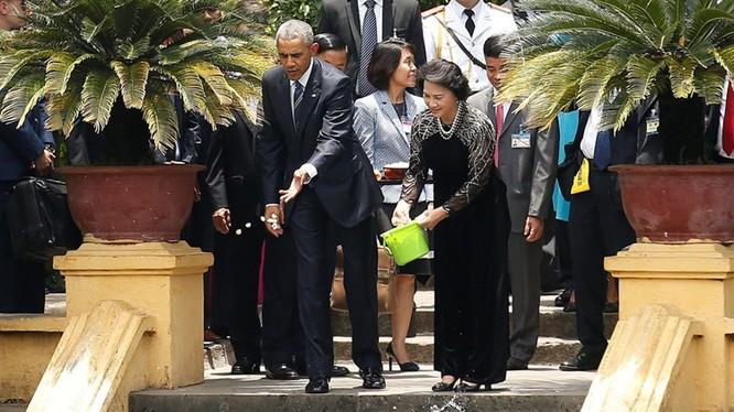 Tổng thống Mỹ và Chủ tịch Quốc hội Nguyễn Thị Kim Ngân cho cá trong ao cá Bác Hồ ăn. (Ảnh: Reuters)
