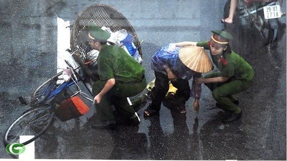 Các chiến sĩ công an giúp đỡ cụ già bị ngã xe giữa đường