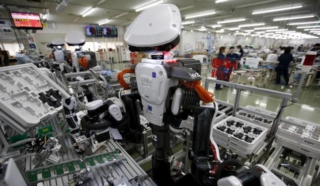 Robot làm việc cạnh con người trong dây chuyền lắp ráp tại một nhà máy của Glory, miền Bắc Tokyo (Nhật Bản) hôm 1/7/2015. Ảnh: Reuters