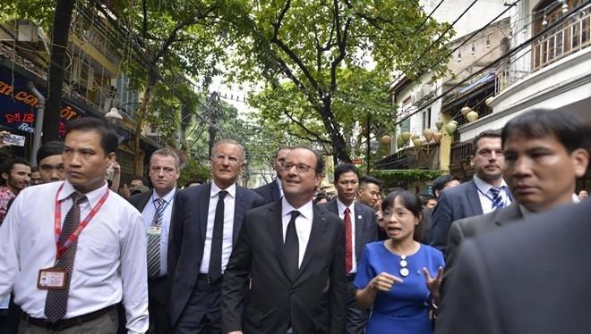 Tổng thống Pháp hòa mình vào dòng người đông đúc đi thăm khu 36 phố phường ở Hà Nội.