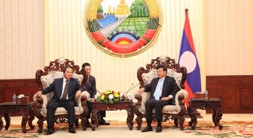 Thủ tướng Chính phủ Lào Thongloun Sisulith (phải) tiếp thân mật Bộ trưởng Trương Minh Tuấn.