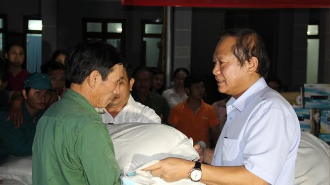 Bộ trưởng Trương Minh Tuấn ân cần trao quà cho các gia đình chịu thiệt hại vì đợt lũ lụt vừa qua.