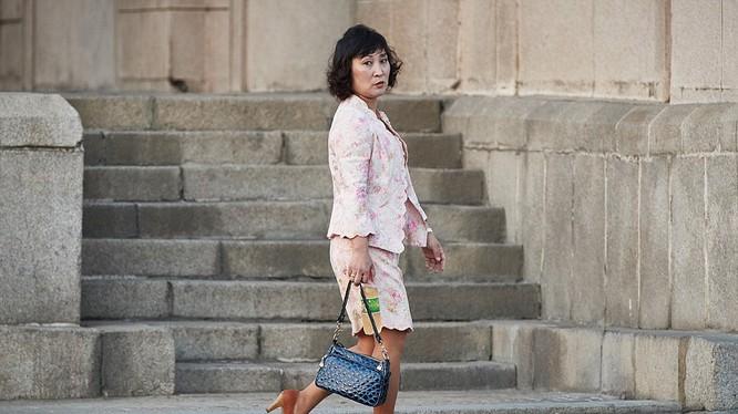 Một phụ nữ ăn mặc thời trang, tay cầm túi xách da cá sấu, chân đi giày cao gót đang dạo bộ trên đường phố Bình Nhưỡng - Triều Tiên.