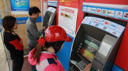 Người dân Hà Nội rút tiền từ cây ATM dịp cuối năm. Ảnh: Như Ý