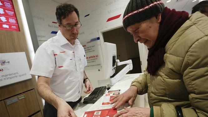 Một cụ ông tới mua tem Tết Đinh Dậu 2017 tại bưu cục Vancouver (Canada).