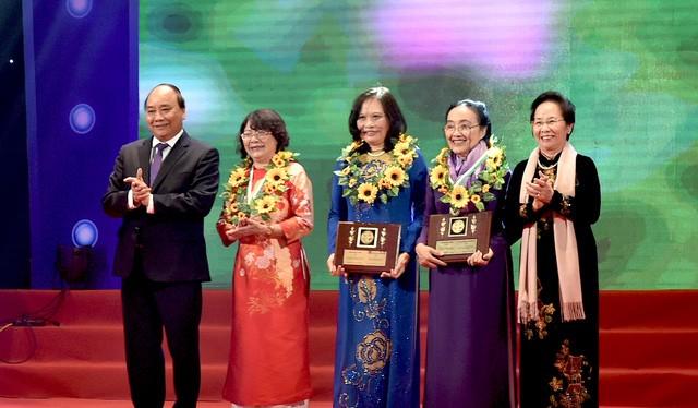 Thủ tướng Nguyễn Xuân Phúc (trái) và Nguyên Phó Chủ tịch nước Nguyễn Thị Doan (phải) tặng hoa cho các phụ nữ điển hình tiên tiến.